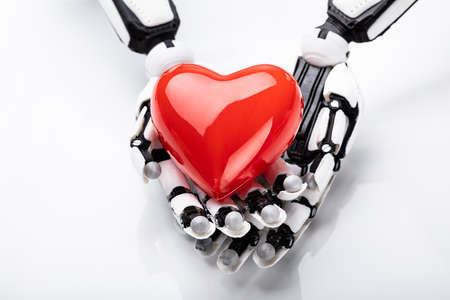 Elevated View Of Robotic Hand Holding Red Heart