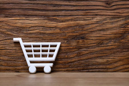 White Shopping Cart Leaning On Wooden Wall Фото со стока
