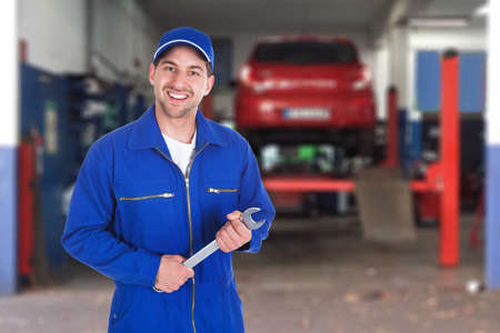Portrait Of A Happy Male Car Mechanic Holding Spanner