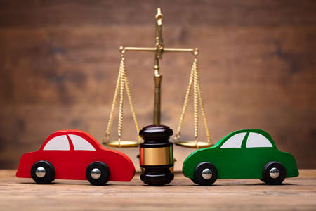 Close-up Of Two Red And Green Car In Front Of Justice Scale On Wooden Desk Reklamní fotografie