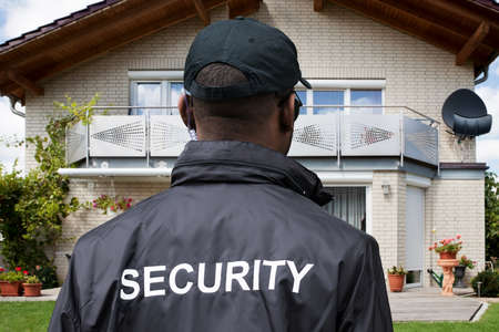 Rear View Of A Male Security Guard In Front Of House Фото со стока
