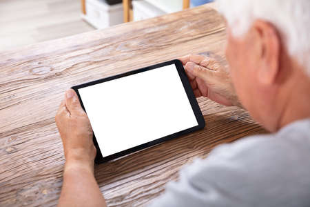 Close-up Of A Senior Man Using Digital Tablet With Blank White Screen