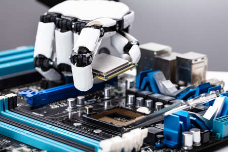 Close-up Of A Robotic Hand Placing Processor Chip In Motherboard Фото со стока