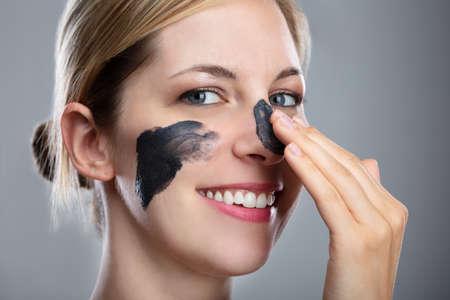 Porträt einer lächelnden jungen Frau, die Aktivkohle-Maske auf ihrem Gesicht anwendet