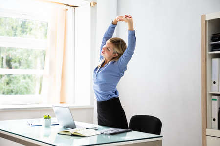 Beautiful Young Businesswoman Stretching Her Arms At Workplace