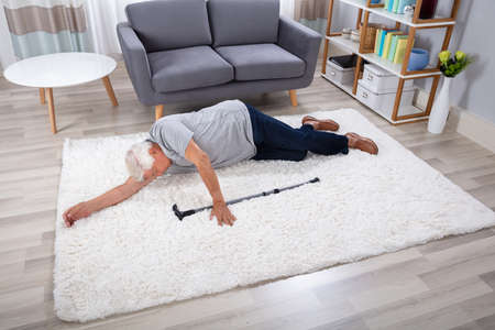 Unconscious Senior Man With Walking Stick Lying On Carpet At Home