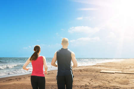 Rear View Of An Athletic Couple Running At Beach During Sunny Day