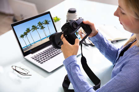Female Editor Looking At Couple Photograph In DSLR Camera With Laptop On Desk Фото со стока
