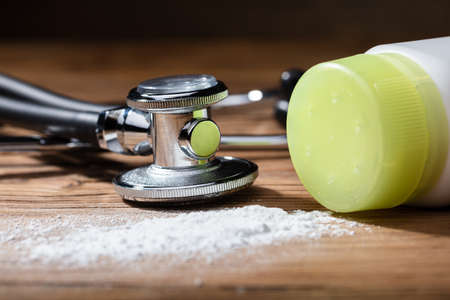 Close-up Of Spilled Talcum Powder And Stethoscope On Wooden Background Фото со стока