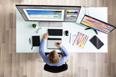 Vista in elevazione della femmina Editor utilizzando la tavoletta grafica mentre si lavora sul computer in ufficio