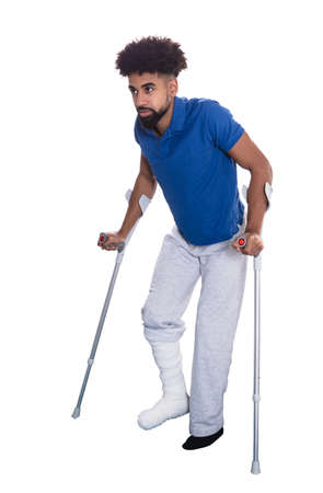 Man With Broken Leg Using Crutches On White Background