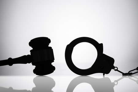 Silhouette Of Handcuff Near Gavel With Sounding Block On Reflective Background