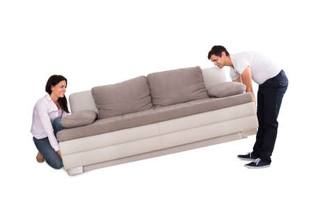 Young Couple Lifting Sofa On White Background