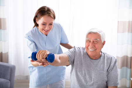 Young Female Nurse Helping Happy Senior Man With Dumbbell Exercise