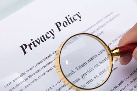 Close-up Of A Womans Hand Holding Pen Over Privacy Policy Form