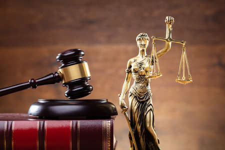 Close-up Of Golden Lady Justice Near Wooden Gavel Over Law Book