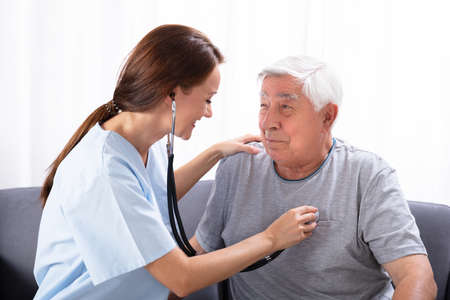 Smiling Young Nurse Examining Senior Man With Stethoscope At Home
