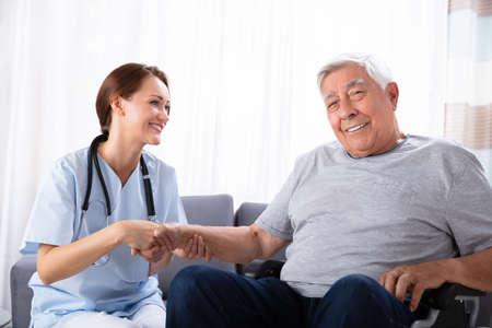 Portrait Of A Smiling Senior Man Sitting On Wheelchair With Female Nurse