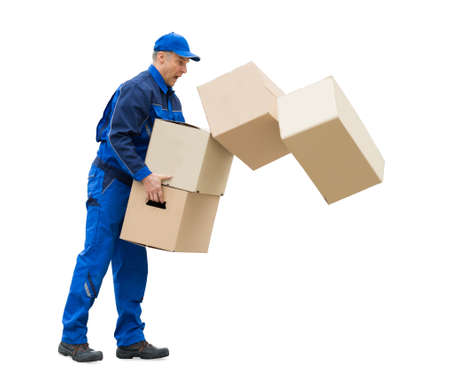 Side View Of A Mature Man With Falling Stack Of Cardboard Boxes On White Background