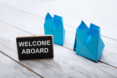 Close-up Of Welcome Aboard Text On Slate Over Wooden Desk