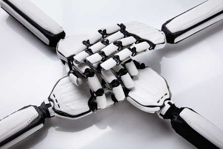 Close-up Of Robot Stacking Their Hands On White Background