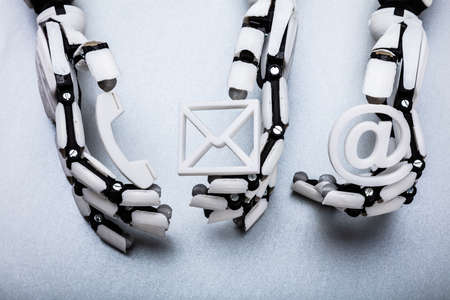 Robotic Hand Holding Various Contact Icons On Gray Background Фото со стока