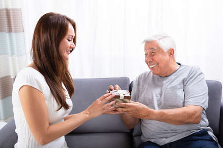 Woman Giving Gift To Her Happy Father Sitting On Sofa Фото со стока