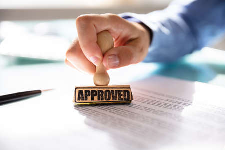 Close-up Of A Businesswomans Hand Stamping On Approved Contract Form