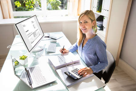 Young Businesswoman Calculating Bill With Computer And Laptop On Desk