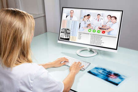 Female Dentist Video Conferencing With Her Colleagues On Computer In Clinic Banque d'images