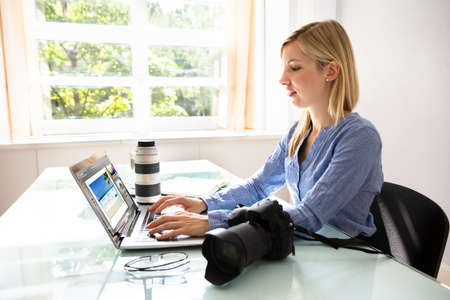 Female Editor Working On Laptop With DSLR Camera On Desk Фото со стока