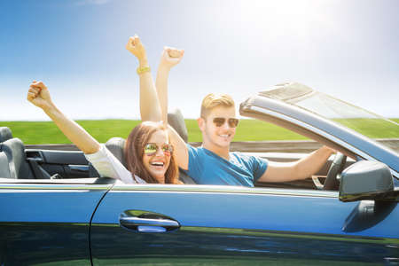 Young Couple Wearing Sunglasses Traveling In The Car