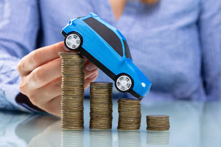Businesswomans Hand Driving Blue Car On Declining Stacked Coins Over Desk