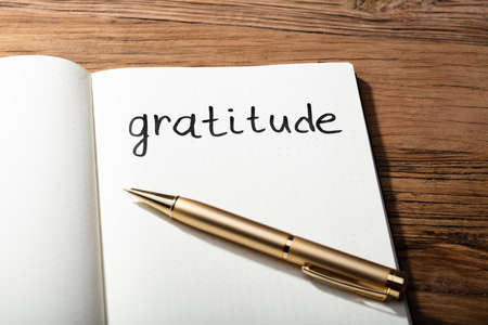 Close-up Of Gratitude Word With Pen On Notebook Over Wooden Desk Фото со стока
