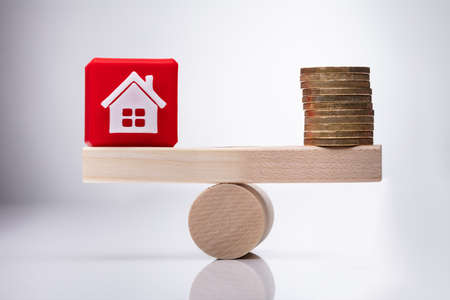 Red House Model Cubic Block And Stacked Golden Coins Balancing On Wooden Seesaw