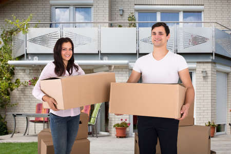 Portrait Of A Happy Young Couple Holding Cardboard Box In Front Of Their House