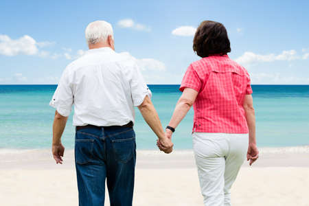 Senior Couple Holding Hands Walking At Beach