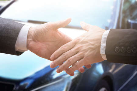 Close-up Of Two Businesspeople Shaking Hands Near Car