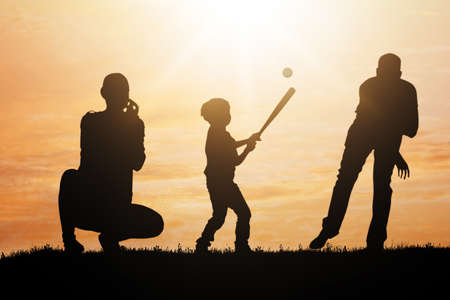 Silhouette Of Family Playing Baseball In Park At Sunset