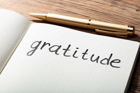 Close-up Of Gratitude Word With Pen On Notebook Over Wooden Desk Stockfoto