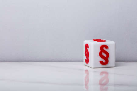 White Cubic Block With Red Paragraph Symbol On Reflective Desk Stok Fotoğraf - 110280409