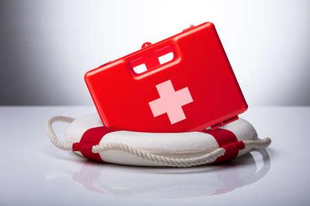 Nahaufnahme von Erste-Hilfe-Kasten und Rettungsring auf reflektierendem Schreibtisch