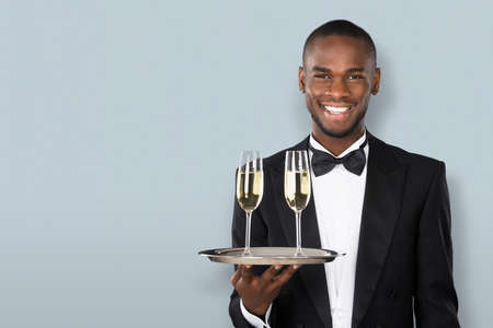 Portrait Of A Smiling African Waiter Holding Champagne Drink On Gray Background