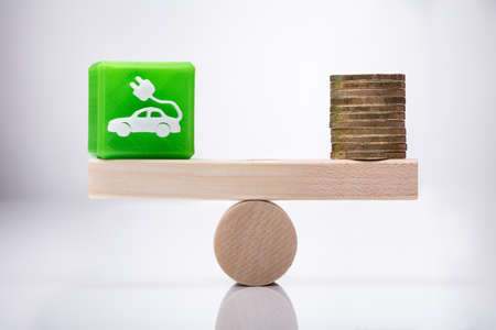 Green Eco Car Icon Cubic Block And Coins Balancing On Wooden Seesaw Over Reflective Desk