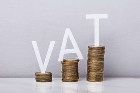 White VAT Word On Growing Stacked Coins In Front Of Wall