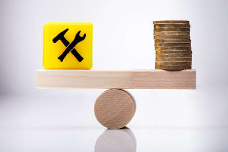 Yellow Under Construction Icon Cubic Block And Stacked Coins Balancing On Wooden Seesaw Stockfoto