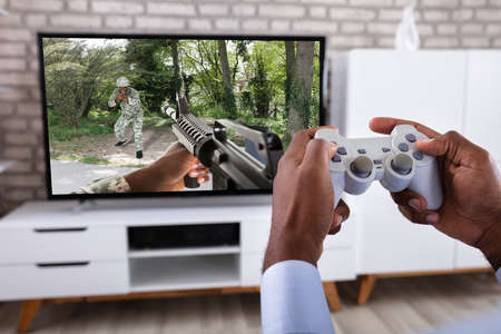 Close-up Of A Man's Hand Playing Action Game On Television At Home