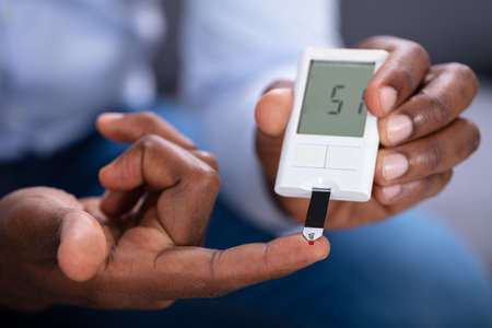 Nahaufnahme der Hand eines Mannes, die Blutzuckerspiegel mit Glukometer prüft Standard-Bild