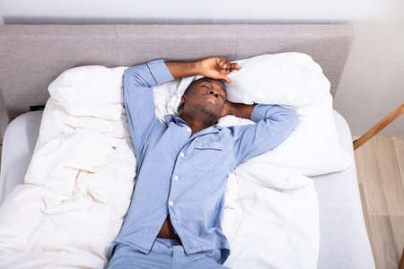 High Angle View Of Young African Man Sleeping On Bed In Bedroom