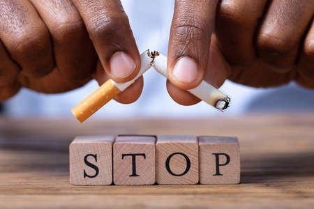 Close-up Of A Mans Hand Breaking Cigarette Over Wooden Stop Blocks